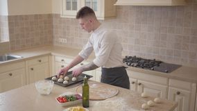 Young pizza maker in cook uniform putting dough balls for pizza on baking tray in the kitchen. Food preparation concept. Young skillful pizza maker in cook stock video footage