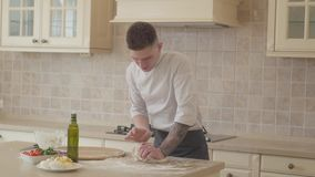 Young pizza maker in cook uniform skillfully and fast kneeding dough for pizza in modern kitchen. Olive oil, tomatoes. Hands of young pizza maker in cook uniform stock video footage
