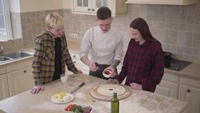 Young pizza maker teaching his friends how to make pizza in the kitchen at home. Confident pizzaiolo applying tomato. Sauce on dough using spoon. Pizza cooking stock video