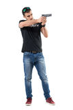 Young plain clothes undercover policeman pointing gun away Stock Images
