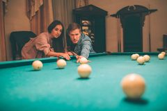 Young player stand in angled position and aiming to break ball. He looks concentrated. Brunette stand besides him and look at. Billiard balls. Guy hold cue in stock images