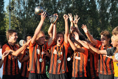 Young players keep a cup Royalty Free Stock Image