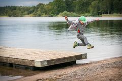 Young playful caucasian boy running in mid-air making a jump from a jetty to the beach. royalty free stock photos