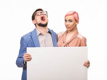 Young  playful couple showing presentation pointing placard Royalty Free Stock Images