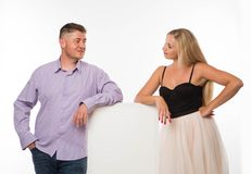 Young playful couple showing presentation pointing placard. Royalty Free Stock Photos
