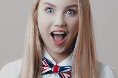 Young playful cute blonde with bow tie opens her mouth in surprise stock image