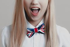 Young playful cute blonde with bow tie opens her mouth in surprise stock photography