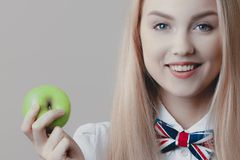 Young playful cute blonde smiles with green apple in her hand royalty free stock photos