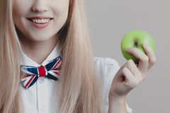 Young playful cute blonde smiles with green apple in her hand royalty free stock image