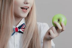 Young playful cute blonde smiles with green apple in her hand stock images