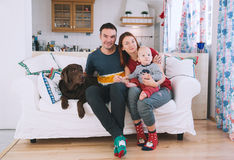 A young playful family at home on the couch. Happy parents with baby and dog on the couch at home interior. Lifestyle, family and togetherness concept. Portrait Royalty Free Stock Photography
