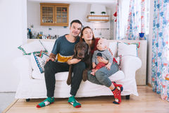 A young playful family at home on the couch. Happy parents with baby and dog on the couch at home interior. Lifestyle, family and togetherness concept. Portrait Royalty Free Stock Photo