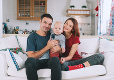 A young playful family at home on the couch. Happy parents with baby on the couch at home interior. Lifestyle, family and togetherness concept. Portrait a young Stock Image