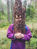 Young playful girl holding a piece of tree bark as face mask. Portrait of funny young girl holding a piece of tree bark as face mask outdoors in the forest Stock Images