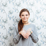 Young playful hipster woman posing against wall with vintage wallpapers pattern Royalty Free Stock Image