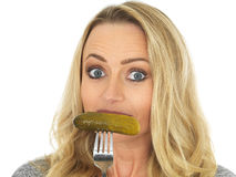 Young Playful Woman Holding a Gherkin on a Fork Stock Images
