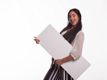Young playful woman showing presentation, pointing on placard Royalty Free Stock Photography