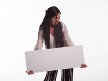 Young playful woman showing presentation, pointing on placard Royalty Free Stock Photo