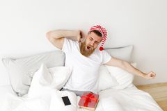 Young pleasant looking male stretches and yawns in bed, awakes early in morning, sits in comfortable bed, surrounded. With modern smart phone and wrapped gift Royalty Free Stock Images