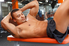 Young pleasant man doing abdominal crunches in gym Stock Images