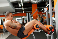 Young pleasant man doing abdominal crunches in gym Stock Photos