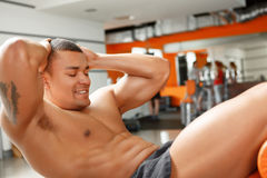 Young pleasant man doing abdominal crunches in gym Stock Photo