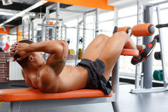 Young pleasant man doing abdominal crunches in gym Stock Photography