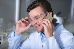 Young pleasant practitioner talking by cellphone and smiling. Good news. Pleasant handsome unshaken practitioner in a special glasses and uniform sitting in the Stock Photos