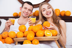 Young pleasant smiling couple with ripe oranges and freshly juice royalty free stock photography