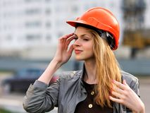 The young pleasant smiling girl. With long hair costs against the building under construction Stock Images