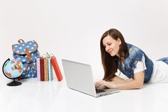 Young pleasant woman student in denim clothes working on laptop pc computer lying near globe, backpack, school books. Isolated on white background. Education in stock photography