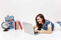 Young pleasant woman student in denim clothes working on laptop pc computer lying near globe, backpack, school books. Isolated on white background. Education in stock photos
