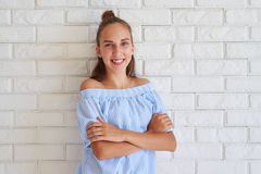 Young pleased girl folded her arms while standing against white Royalty Free Stock Photos