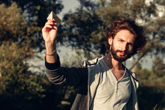 Young pleased guy playing with paper airplane Royalty Free Stock Photos