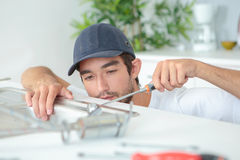 Young plumber fitting sink. Young plumber fitting a sink Stock Photos