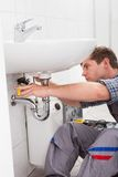 Young plumber fixing a sink in bathroom Royalty Free Stock Photos