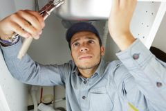 Young plumber fixing sink. Young plumber fixing the sink stock photos