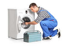 Young plumber fixing a washing machine. On white background Stock Photo