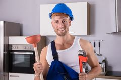 Young Plumber Holding Wrench And Plunger In Kitchen royalty free stock photos