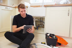 Young plumber with tablet computer fixing sink in kitchen Royalty Free Stock Photos