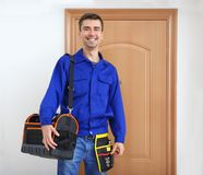 Young plumber with tool bag and belt,. Indoors royalty free stock images