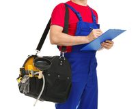 Young plumber with tool bag and clipboard. On white background stock photo
