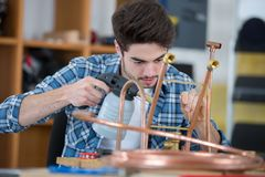 Young plumber using welding gas torch to solder copper pipes. Man stock photos