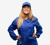 Young woman with plumber clothes isolated over grey background royalty free stock image