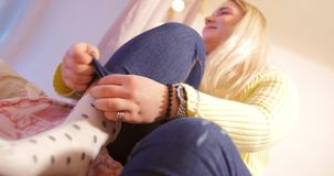 Young plump blonde girl in a yellow sweater puts on a white polka dot sock, smiles into the camera and shows tongue. Teenager, pastel colors stock video