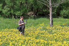 Young plump man in a meadow with blooming dandelions. Conducts video recording on a smartphone installed on a gimbal. Near the. River flows stock images