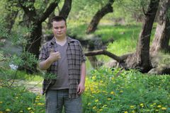Young plump man stands with his back to the river. Raised up the thumb. Shows like. In the park among the bright green foliage.  royalty free stock images