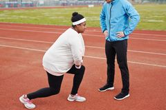 Knee bending. Young plump women in activewear bending her knees during physical exercise with her trainer standing in front Royalty Free Stock Photography