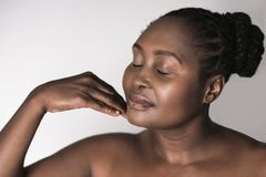 Young African woman with her eyes closed touching her chin. Young plus size African woman with a beautiful complexion standing against a white background with Stock Image