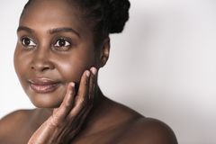 Young African woman smiling and touching her perfect skin. Young plus size African woman with a perfect complexion smiling while standing against a white Stock Photography